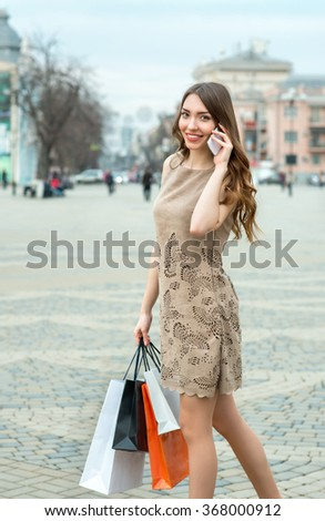 Smiling  young woman with shopping bags  talking on cell phone at the street in the city. Fashion and city style. Facial expression. - stock photo