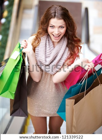 Smiling young woman with shopping bags walking the stairs at mall - stock photo