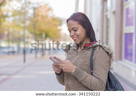 Smiling young woman with smart phone in the street.