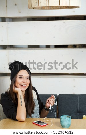 Smiling young woman, with tattoo on her arm, wearing in black and white coat and hat, sitting on the table with smart phone, earphones and cup of coffee, in cafe with wooden walls, waist up - stock photo