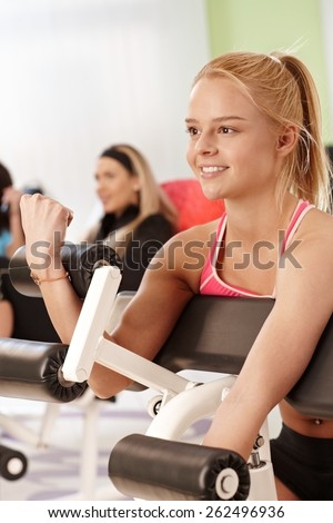 Smiling young woman working out at the gym on exercise machine. - stock photo