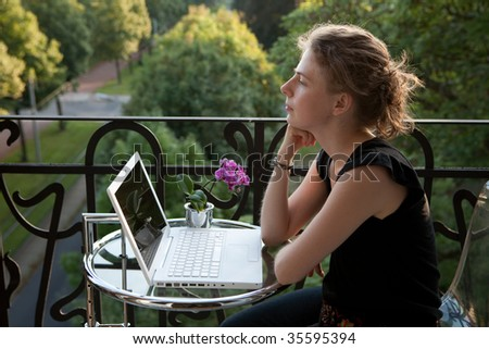smiling young woman writing on a white modern laptop computer on a balcony in art nouveau - stock photo