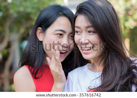 Smiling young women friends gossiping and whispering secrets - people, communication and friendship concept
