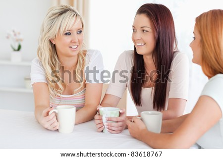 Smiling young Women sitting at a table with cups in a kitchen