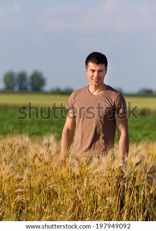 Smiling young worker in t shirt standing in golden barley field - stock photo
