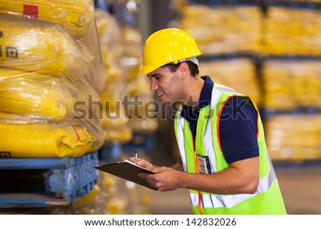 smiling young worker recording rice stock before delivery - stock photo