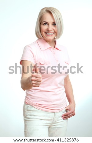 Smilling attractive middle aged woman showing thumbs up, okay. Isolated - stock photo