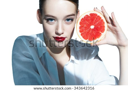 Smilling brunette woman with mottled orange slice / close-up of an attractive girl of the European appearance in a white shirt holding a cut piece of orange - isolated on white background - stock photo