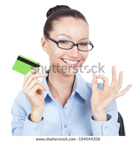 Smilling businesswoman on workplace with credit card in hand - stock photo
