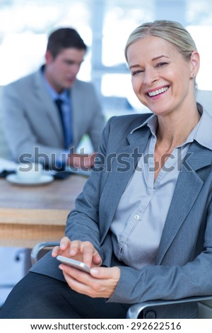 Smilling businesswoman texting on her mobile phone in an office