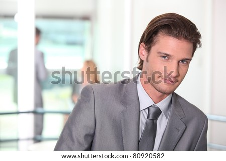 Smirking young executive in a office building - stock photo