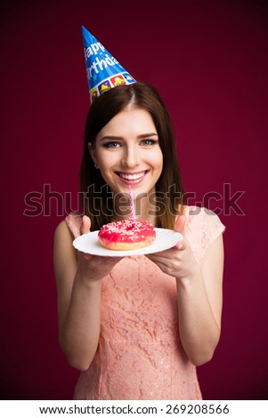 Smling young woman holding donut with candle over pink background and looking at camera - stock photo