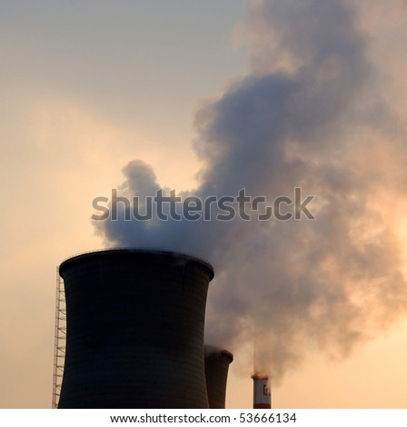 Smoke and steam from the plant pipes. Sunset. - stock photo