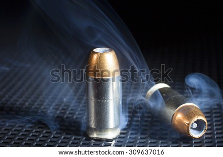 Smoke around a pair of handgun cartridges with hollow point bullets - stock photo