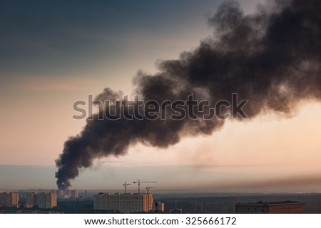 Smoke at sky of morning city. Big fire at apartment house. Warm sunrise colors. - stock photo