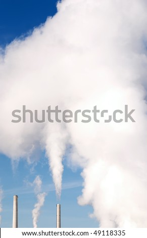 Smoke billowing into deep blue sky from smoke stacks