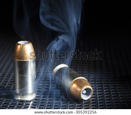 Smoke circling around a pair of handgun cartridges with hollow point bullets - stock photo