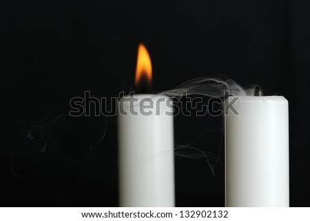 Smoke coming from a blown out candle with a burning candle in background