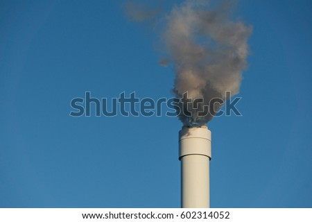 Smoke coming from a chimney, rising against a clear nice blue sky
