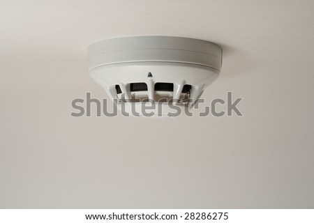 Smoke detector fitted on a ceiling - stock photo