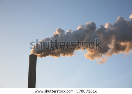 Smoke from pipes against the blue sky.
