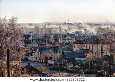 Smoke from the burned leaves over the small city