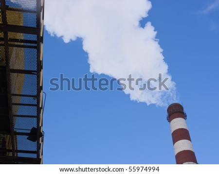 Smoke from the pipe on a background of blue sky - stock photo