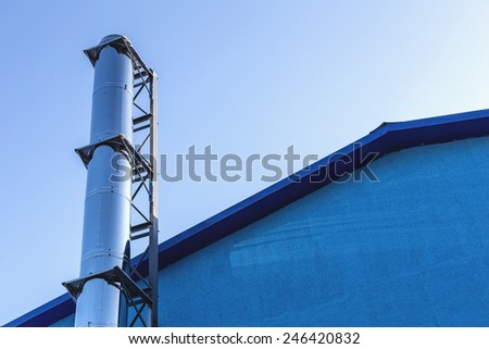 Smoke metal chrome pipe on rooftop  against blue sky background