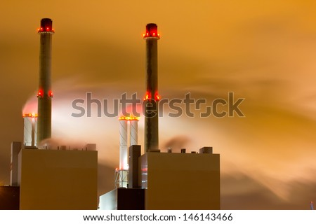 Smoke originating from a large power-station seen at night - stock photo