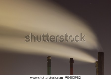 Smoke originating from an industrial plant seen at night - stock photo