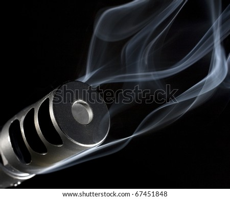 smoke pouring out of the muzzle brake on a precision rifle - stock photo