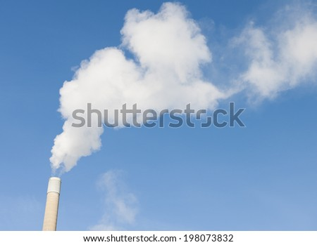 Smoke rising from an industrial chimney - stock photo