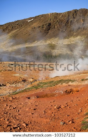 Smoke rising from hot springs in Iceland - stock photo