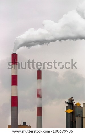 Smoke rising from power plant against sky - stock photo