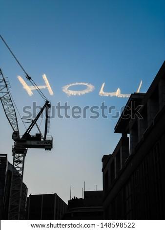 Smoke show write 'HOW' in the sky . - stock photo