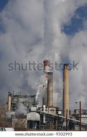 Smoke stacks billowing smoke and pollution - stock photo