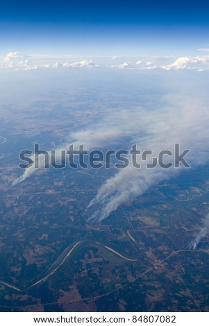 Smoke tails rising to the sky from forest wild fires - stock photo