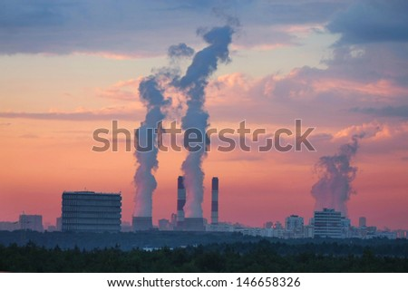 Smoke under the sunset sky in Moscow - stock photo