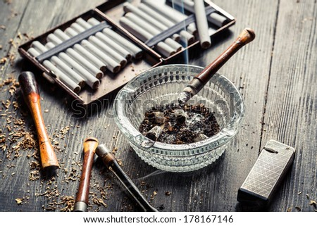 Smoked a pipe on the background of cigarette - stock photo