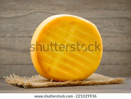 Smoked cheese wheel on wooden table - stock photo