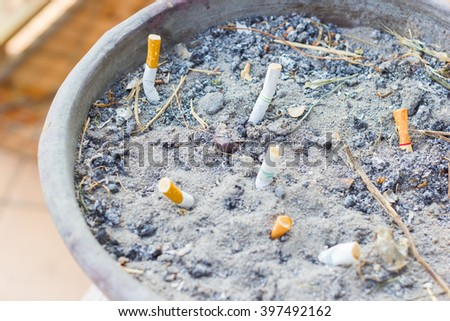 Smoked Cigarettes Butts in a Public Ashtray, selective focus. - stock photo
