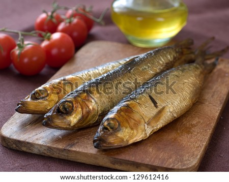 Smoked fish (herring or sardine) on board, selective focus - stock photo