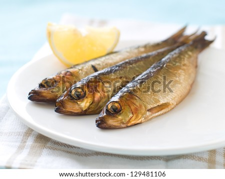 Smoked fish (herring or sardine) on plate, selective focus - stock photo