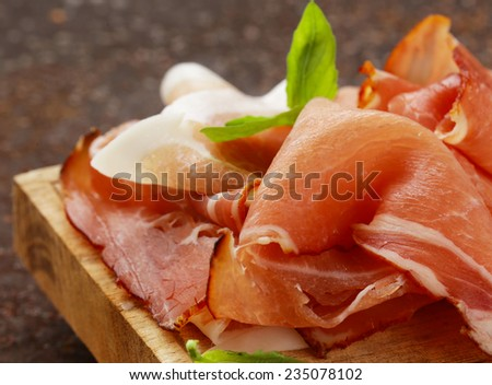 smoked ham jamon (Parma) with basil leaves on  wooden board - stock photo