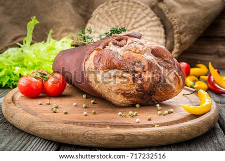 Smoked ham with herbs and spices on a wooden table