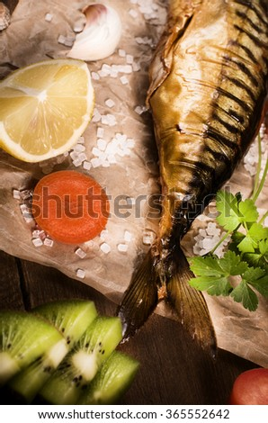 Smoked mackerel with lemon on paper, top view cocking background. - stock photo