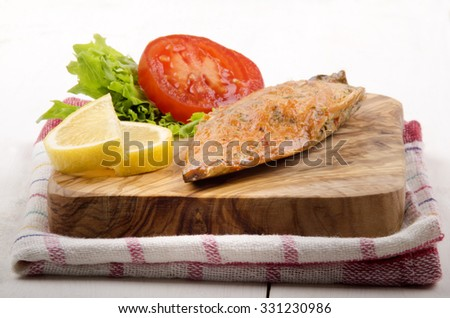 smoked mackerel with salad, tomato and lemon on a wooden board - stock photo