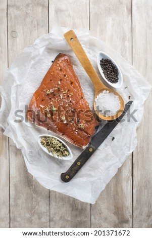 Smoked marinated salmon and ingredients on the kitchen table - stock photo