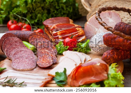 Smoked meat, bacon and sausages on wooden board