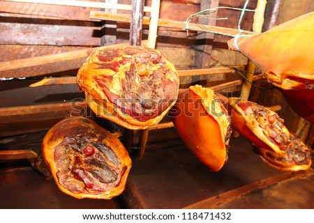 smoked meat hanging in the smokehouse - stock photo